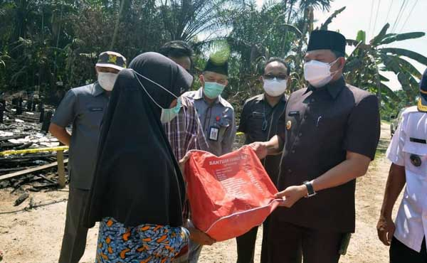 Wakil Bupati Hairan, SH Menyerahkan Bantuan Kepada Ibu Husnah keluarga tertimpa musibah kebakaran di RT.07 Dusun Rantau Panjang Desa Kelagian Kecamatan Tebing Tinggi, Rabu (28/07/21). FOTO : PROKOPIM