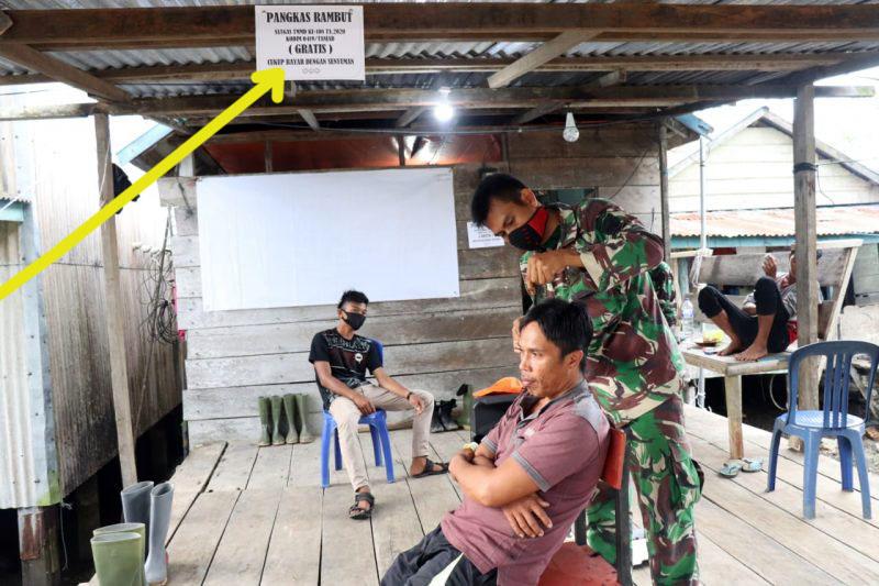 FOTO : Anggota Satuan Tugas (Satgas) TNI Manunggal Membangun Desa (TMMD) ke 108 Kodim 0419/Tanjab Saat Memangkas Rambut Warga di lokasi TMMD, Rabu (08/07/20).