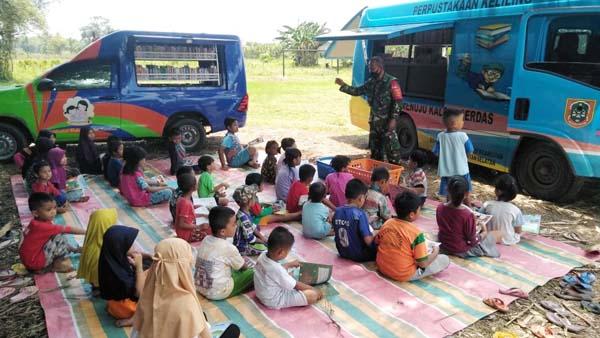 Dansatgas TMMD Ke-112 Kodim 1002/HST, Letkol Inf Muh. Ishak HB Tengah Bersama Anak-anak dengan Perpustakaan Keliling, Selasa, (12/10/21).