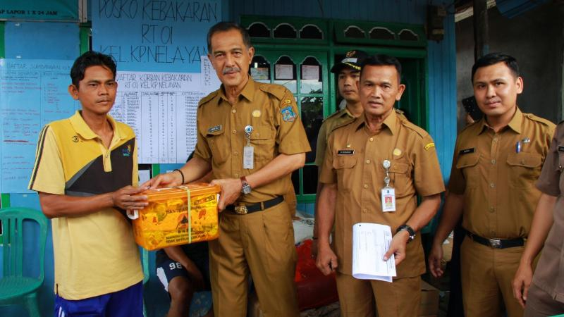 FOTO : Sekda Drs. H. Ambok Tuo, MM Menyerahkan Bantuan Korban Kebakaran di Posko Tanggap Darurat kebakaran, Senin (03/12/18)