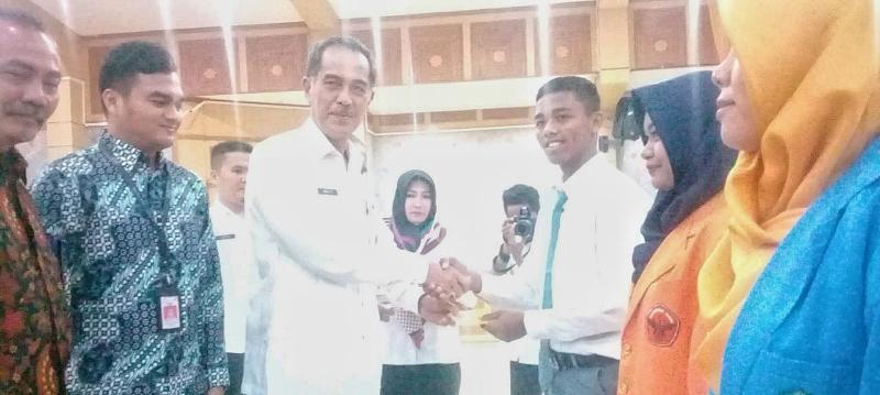 FOTO : Sekda Tanjab Barat Drs. H. Ambok Tuo, MM Secara Simbolis Serahkan Bantuan Beasiswa, Rabu (05/12/18)