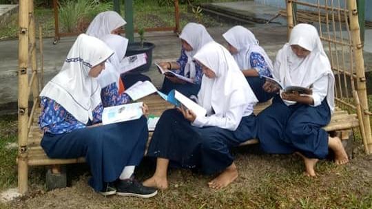 FOTO : Sejumlah siswi membaca buku di saung baca yang dibangun oleh sekolah dan masyarakat, saung tersebut kini bisa dinikmati oleh siswa SMPN 11 Batang Hari sebagai tempat membaca, Senin, (03/12/18)