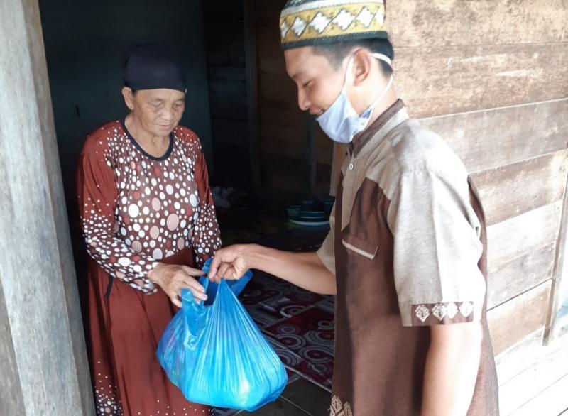 FOTO : HB Saat Baksos Membagikan Paket Sembako dari Polres Tanjab Barat di RT 016 Bina Karya Selatan, Jumat (29/05/20).
