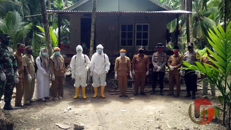 FOTO : Tim Gugus Tugas Kecamatan Senyerang Melakukan Penyemprotan Disinfektan Sekitar Rumah Pasien Rekatif Rapid test yang meninggal di RSUD KH. Daud Arif di Desa Sungai Landak, Minggu (30/08/20).